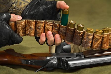 hunter adds ammunition for the shotgun in his bandolier, closeup
