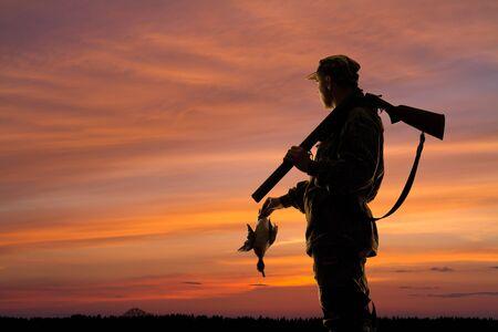 silueta del cazador de patos con pato caído en el fondo del atardecer Foto de archivo
