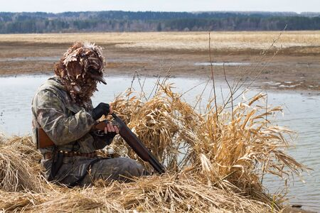 duck hunter charges the shotgun next to the hunting blind of reeds on the lake