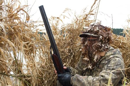 duck hunter with a shotgun waits for waterfowl in a hunting blind of reeds on the lake