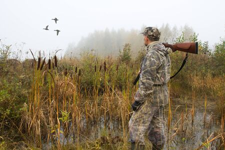a hunter with a shotgun on his shoulder watches the ducks fly away on a foggy morning 免版税图像