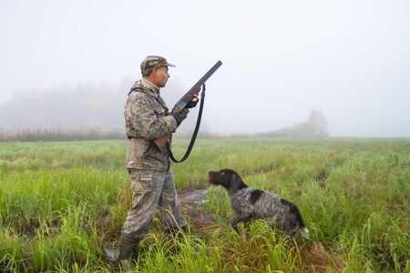 A hunter with a gun and dog stands in a meadow on a foggy morning and holds a shotgun at the ready