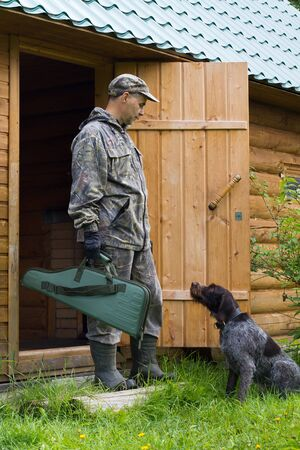 a hunter with a gun case in his hand and a dog stands at the door of a wooden house