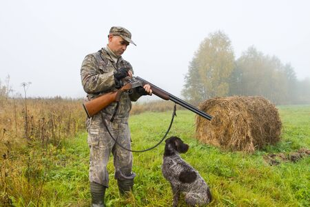 a hunter loads his shotgun on a mown meadow on a foggy morning, a hunting dog sits nearby