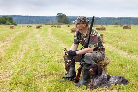 a hunter sits on a mown hay and holds a downed grouse in his hands, a hunting dog lies next to him