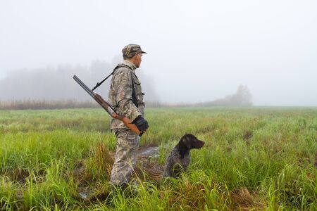 a hunter and his gundog are in a meadow on a foggy morning at the beginning of a hunt 스톡 콘텐츠