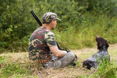 hunter and his dog resting on the mown grass during the autumn hunting