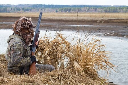 a duck hunter with a shotgun climbs into a shelter of reeds on the river bank 스톡 콘텐츠 - 132671852