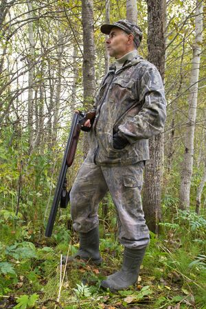 a hunter with a discharged gun in his hand stands in the thicket of aspen in autumn