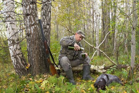 a hunter sits on a fallen tree and pours tea from a thermos, his dog lies next to him