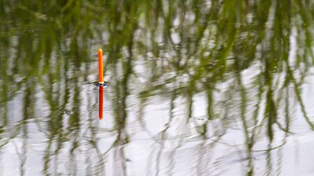 orange fishing float is on the rippling surface of the lake, closeup