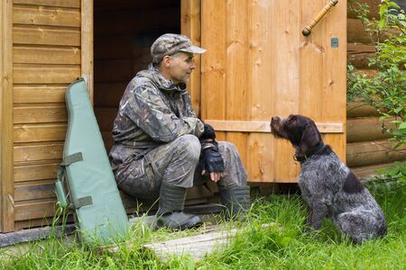the dog sits opposite the hunter at the door of a wooden house, next to a shotgun in a case