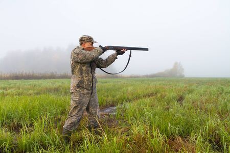 a hunter takes aim with a hunting shotgun in a meadow on a foggy morning at the start of a hunt