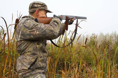 a hunter aims a shotgun among cattails on a foggy morning