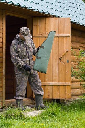 hunter fastens gun case, going hunting, near a wooden house 스톡 콘텐츠