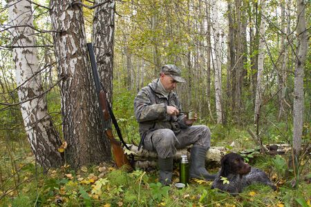 the hunter is sitting on a fallen tree and opens a tin can, and his dog is lying next to him