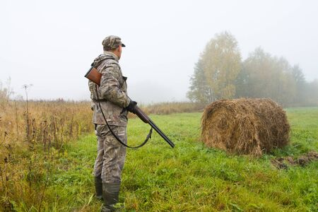 the hunter stands on a mown meadow on a foggy morning next to a roll of hay