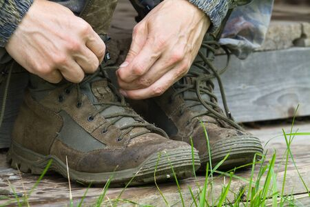 hands of the man tie the laces on his hiking boots on the wooden steps
