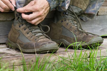 hands of the man lace up his hiking boots on the wooden steps of the house