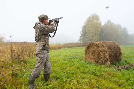 a hunter shoots a flying bird in a mown meadow on a foggy morning