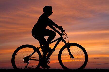 silhouette d'une cycliste féminine équitation contre le ciel coucher de soleil