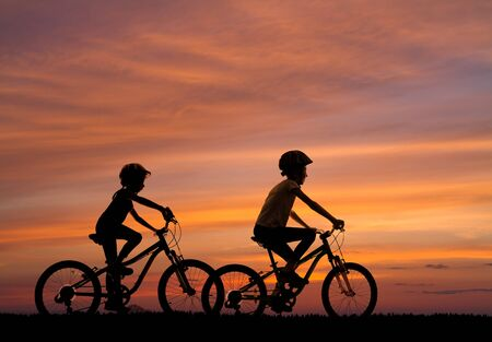 silhouettes of two girls riding bicycles against the background of the sunset sky