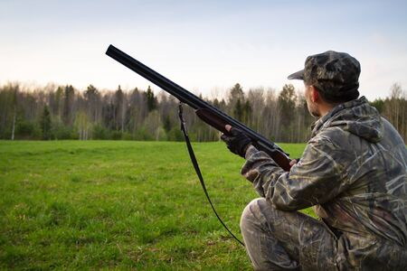 a hunter with a shotgun in his hands knelt down and looks at a forest clearing in the evening in the spring forest