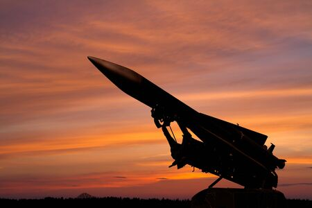 dark silhouette of a Soviet anti-aircraft missile against the background of the dawn sky 版權商用圖片