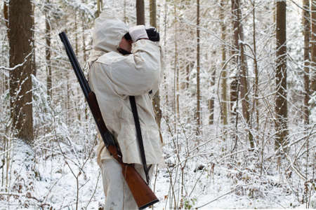 a huntsman dressed in white camouflage stands in the northern forest and looks through binoculars Standard-Bild