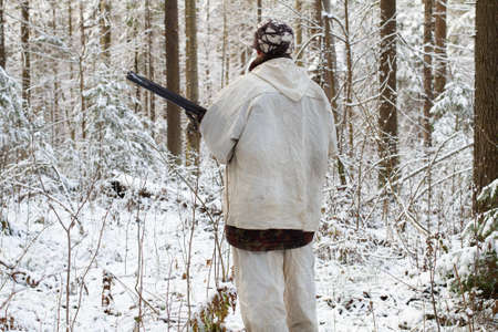 a hunter in white camouflage with a shotgun in his hands stands with his back turned in a snowy winter forest Stok Fotoğraf