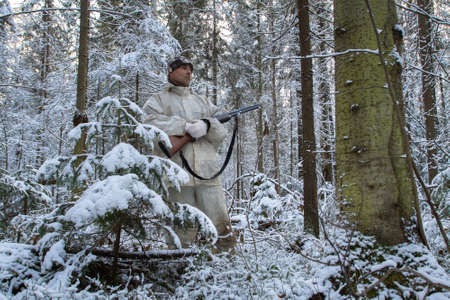 a hunter in white camouflage with a shotgun in his hands stands in a cold winter forest