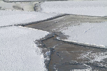 The thin ice sheet split into several large ice floes. Water is visible in the cracks between them. The surface of the ice floes is covered with frost.