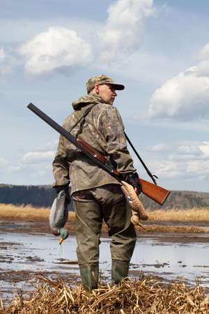 A duck hunter with a duck decoys in his hands stands on the shallow water. He's got a shotgun on his shoulder. Stock fotó