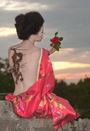 Geisha with dragon tattoo at sunset photo