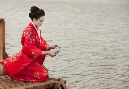Geisha launches origami bird Stock Photo