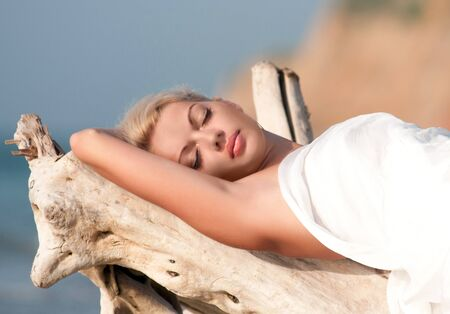 Attractive young woman enjoying the sun while lying on the snag photo