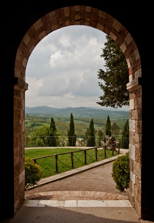 トスカーナの丘を望むアーチの修道院