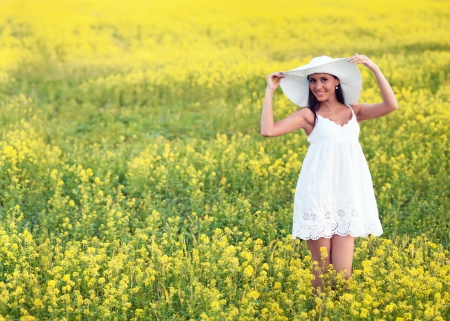 Smiling pretty girl in white in blooming field Stock Photo - 13726011