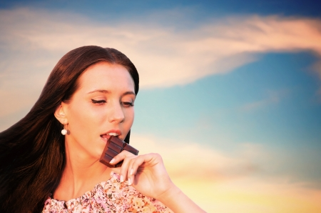 nibbling: Pretty young woman nibbling the bar of chocolate, sunset background