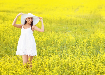 Smiling pretty girl in white in yellow field photo