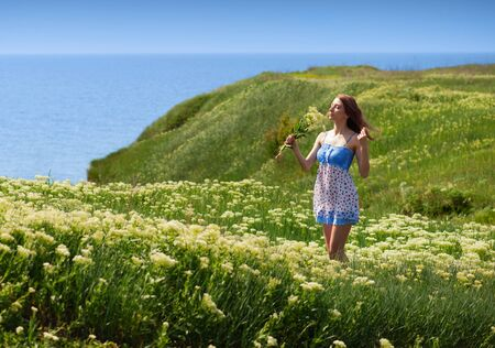 yarrow: Young woman walking among the blooming yarrow at the seaside  Stock Photo