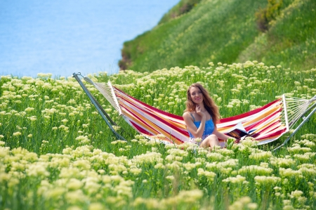 yarrow: Smiling pretty woman sitting in a hammock among the blooming yarrow
