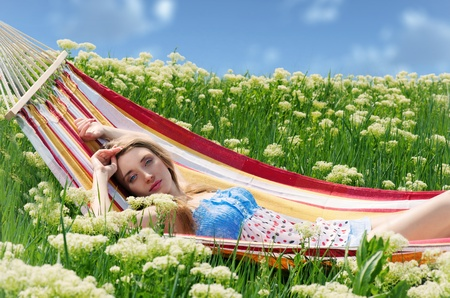 Beautiful blonde woman lying in a hammock among the blooming yarrow in bright spring day photo