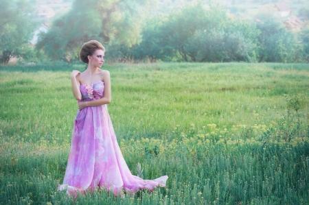 田園背景に風通しの良いピンクのドレスの若い女性のロマンチックな肖像画 写真素材
