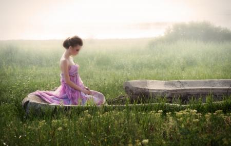 日の出の遺跡に座っている風通しの良いピンクのドレスの若い女性のロマンチックな肖像画 写真素材