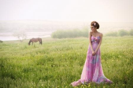 Retrato romántico de la mujer en la mañana de niebla en el río
