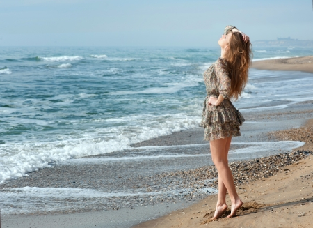 tiptoe: Beautiful woman standing at the seaside and basking in the sunshine