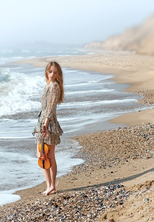 Beautiful delicate girl with violin on the seashore  original  Stock Photo - 13836956