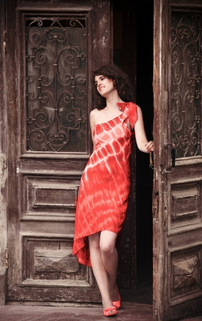 going out: Young pretty woman in red dress going out of old house
