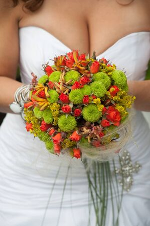 decolletage: Original wedding bouquet with red and green flowers Stock Photo